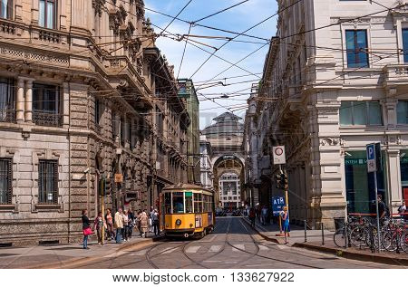 Milan Italy - May 25 2016: View of the Galleria Vittorio Emanuele II by Piazza Cordusio. In the foreground the yellow tram and urban people at a tram stop.