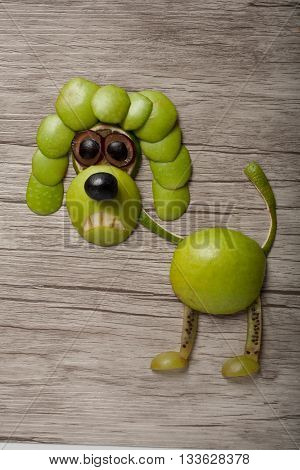 Scared poodle made of apple and grape on desk