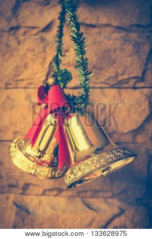 Christmas golden bells with a red bow hanging on the brick wall background. Vintage tone.
