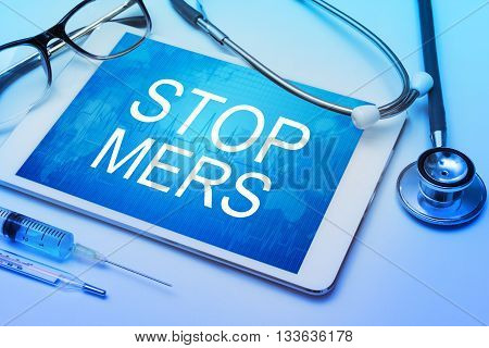 Stop MERS word on tablet screen with medical equipment on background