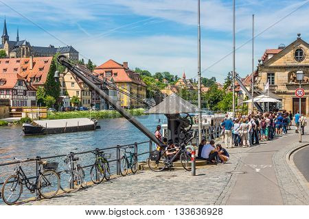 Bamberg Germany - May 22 2016: Old derrick people and excursion boat at Regnitz river in Bamberg Upper Franconia Bavaria Germany.