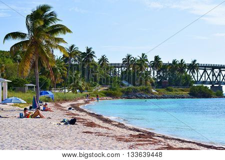 May 15, 2016 in Bahia Honda Key, FL:  Sandy beach at the Atlantic Ocean with people sunbathing surrounded by tropical plants and Palm Trees taken at Bahia Honda Beach where tourists can visit and enjoy leisure recreation on Bahia Honda Key in the Florida