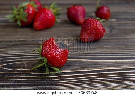 Fresh red bitten strawberry on the wooden background. A few strawberries on the background. Selective focus