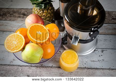 Fresh Juice And Juicer. Photo On Wooden Background