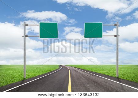 blank road-sign for your advertisement with space for text on road curvewith green grass and blue sky white cloud