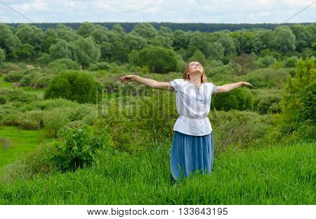 Happy girl with outspread in side hands stands on background of field with bushes and looks up at sky