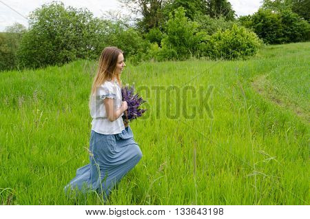 Beautiful girl with basket of wild flowers in her hands is running along field