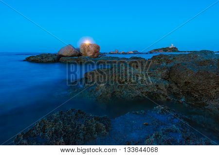 Wide Angle View Of Moon Over Seascape, Rocks And Lighthouse
