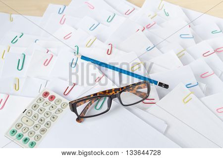 Calculator With Spectacles Put On Stack Of Overload Paper