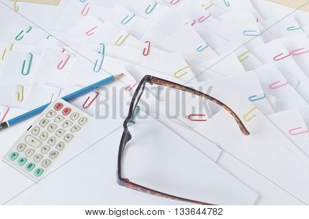 Pencil And Calculator With Spectacles On Stack Of Overload Paper
