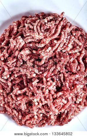 Close up of pinky raw ground beef on a white plate. Ground beef can be used to make hamburgers cutlet, chili con carne or other dishes.