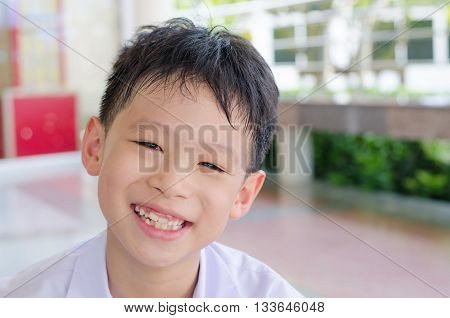 Asian schoolboy in uniform smiles at school