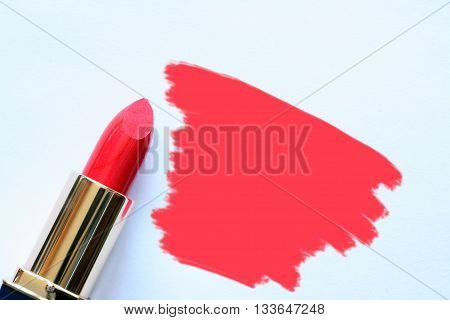 Tube of red lipstick near abstract spot on white background