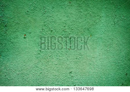 Background made of cracked green paint on the concrete wall