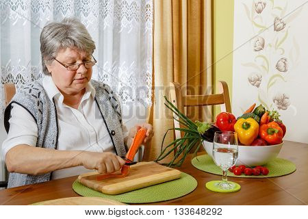 Senior Is Peeling A Carrot At  A Table