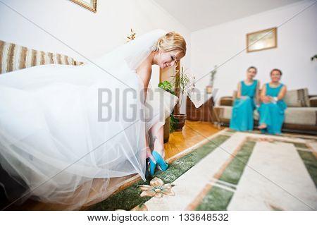 Happy bride put on wedding shoes indoor