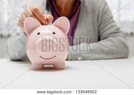 Senior Puts Money Into The Piggy Bank