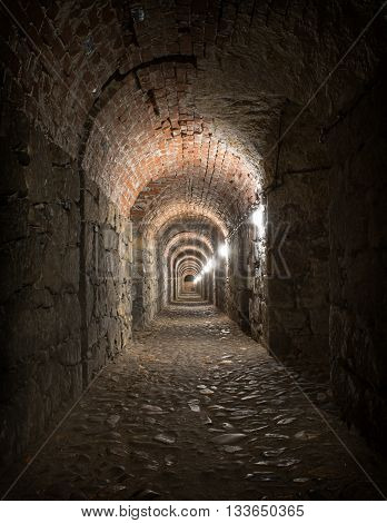 Old medieval brick tunnel with light at the end