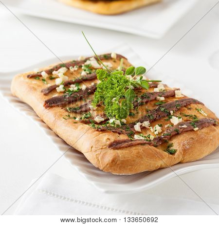 Coca with anchovies. Coca is a typical pastry from the Catalan region of Spain. Similar preparations can be found in other Mediterranean countries.