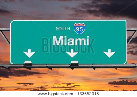 Interstate 95 south to Miami highway sign with sunrise sky.