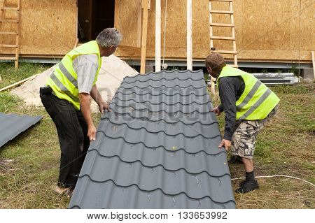 Two workers preparing to install a metal tile on a new wooden house