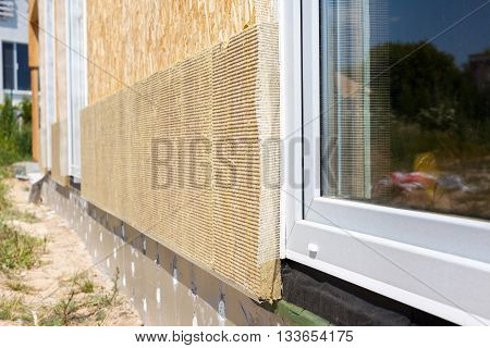 Closeup view on house wall with plastic window and insulation panels