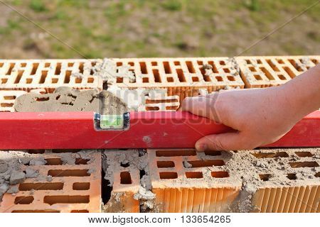 Mason worker measuring with professional level the bricks under construction