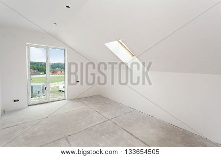 Attic room under construction with gypsum plaster boards and windows
