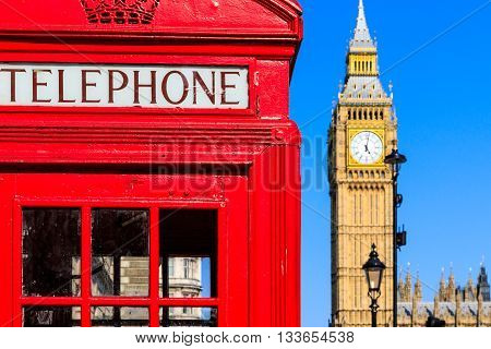 Iconic red telephone box with Big Ben against blue sky in the background