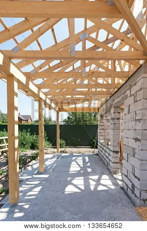 Building house from aerated concrete building blocks. New residential wooden construction home framing against a blue sky