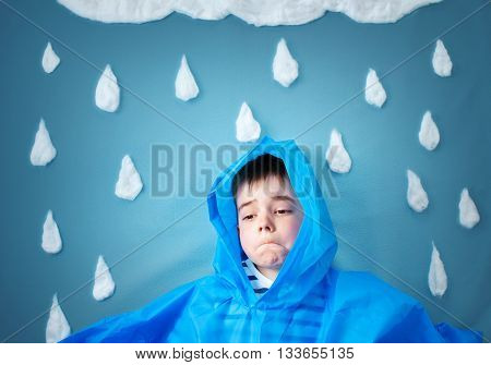 boy on blue background in coat with drop shapes and cloud