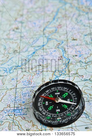 Map and compass. Photo magnetic compass located on a topographic map.