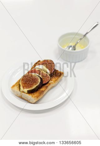 Bruschetta with figs and goat cheese on white table