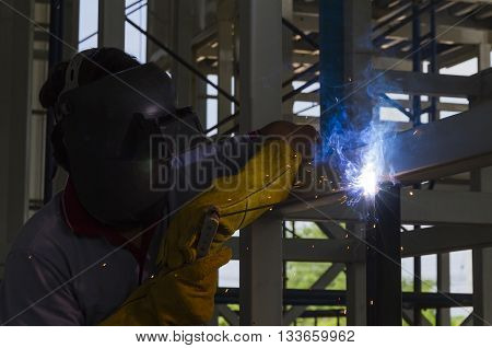 Welders were welding steel structural by shield arc welding - low-key light photo style.