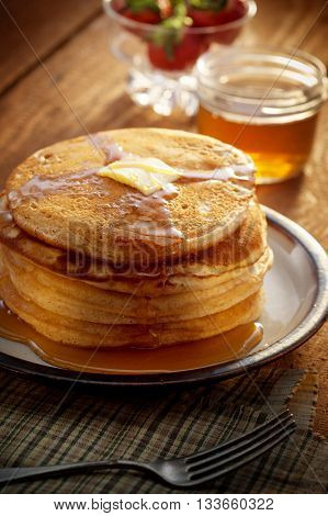 close up view of nice yummy pancakes with honey on table