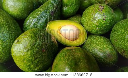 Green Avocados, one of them opened and halved. Pulp and stone are visible.