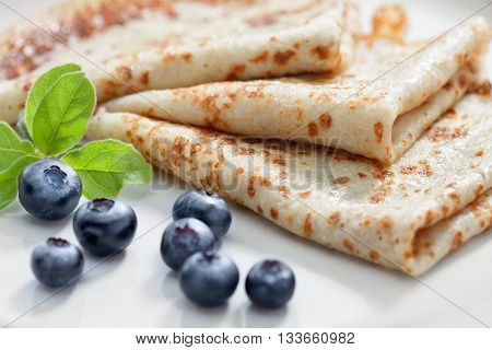 close up view of nice yummy crepes with berry on white