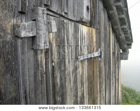 Door of wooden hut in the mountains. Fog in background.