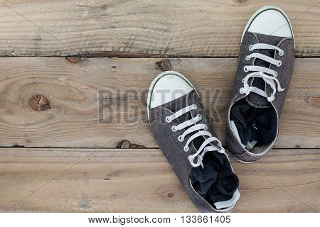 Dirty old shoes on wooden floor with copy space. Top view