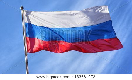 Russian Flag on Flagpole Waving in front of Blue Sky. Flag of Russia.