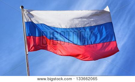 Flag of Russia. Russian Flag on Flagpole Waving in front of Blue Sky.