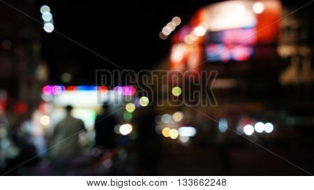 Blurred unfocused scene of market street with people standing front of an illuminated food booth. Red blue violet and white blurry lights.