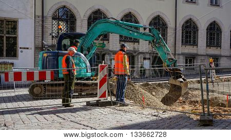 Tallinn, Estonia, 21st April 2016. Construction workers using an excavator for preparation of street in pedestrian zone for reparation.