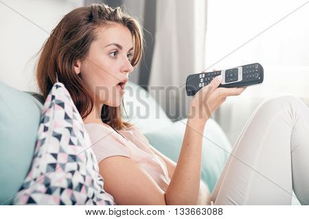 Surprised Young Woman Sitting On Couch At Home And Watching Tv