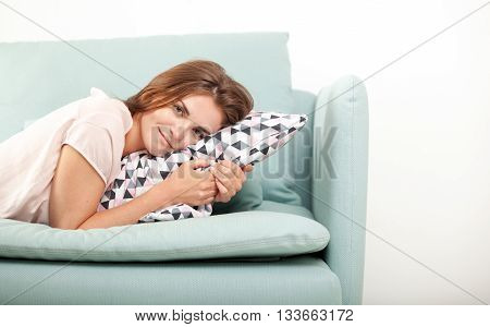 Smiling Young Woman Lying On Couch At Home. Domestic Style Shoot