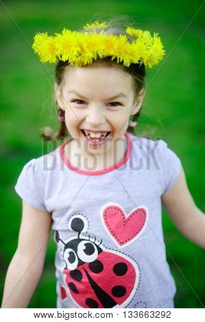 The little girl in a wreath from yellow dandelions. The cheerful girl on a green background. Hair are braided in small braids. On the head a beautiful wreath. The wide smile bares large teeth.