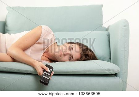 Sleepy Young Woman Lying On Couch Holding Tv Remote Control. Casual Style Indoor Shoot