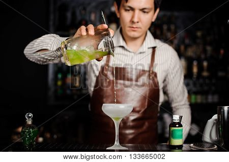 Barman pouring a cocktail into a frozen glass