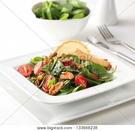 A spinach salad with cherry tomatoes walnuts goat cheese and balsamic vinegar.