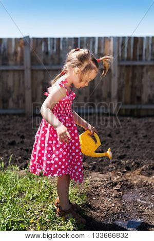Little girl in a red spotted dress with a yellow toy watering-can in the garden. The day is sunny and the shadow are deep. She is watering the garden.